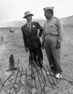Robert Oppenheimer et le général Leslie Richard Groves sur le site de l'essai Trinity en septembre 1945. Les sur-chaussures blanches empêchaient les particules radioactives de s'accrocher aux semelles de leurs chaussures