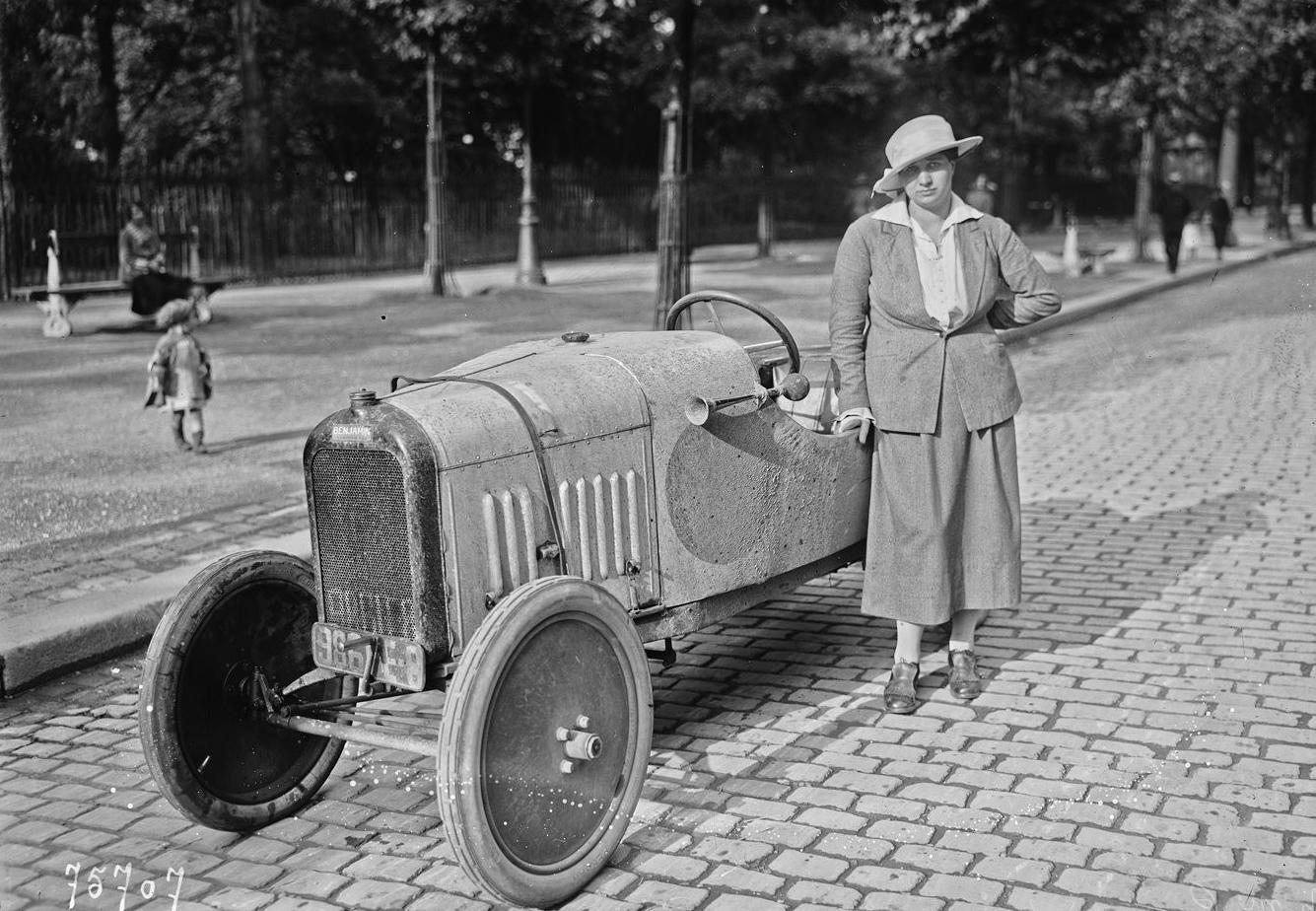 Violette Morris en 1922, en tenue féminine, pose aux côtés d'une automobile Benjamin.