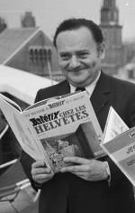 """René Goscinny tenant un exemplaire de l'album """"Astérix chez les Helvètes"""" en 1971."""